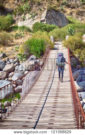 hiker with backpack crossing bridge