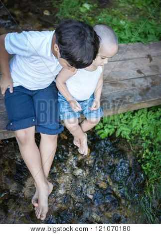 Two brothers friends sitting and enjoying on the wooden bridge by mountain creek in beautiful nature