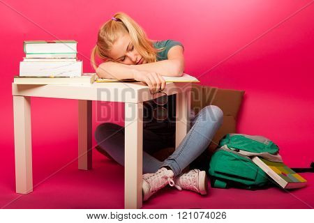 Playful schoolgirl with two hair tails and big eyeglasses sitting behind the small table full of boo
