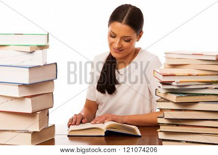 Woman reading behind the table between two pile of books happy to get new knowledge.