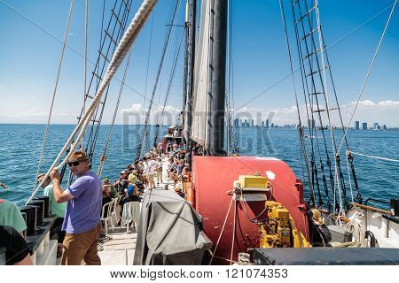 Amazing inviting view of people traveling on a tall ship in the lake Ontario