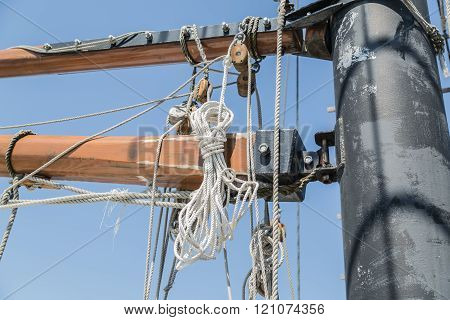 partial view of detailed old tall ship parts and ropes against blue sky background