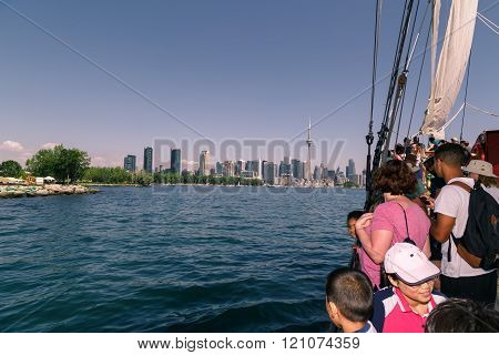 people traveling on a tall ship in lake Ontario toward downtown Toronto skyline
