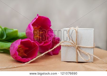 three purple tulip and a box for gift