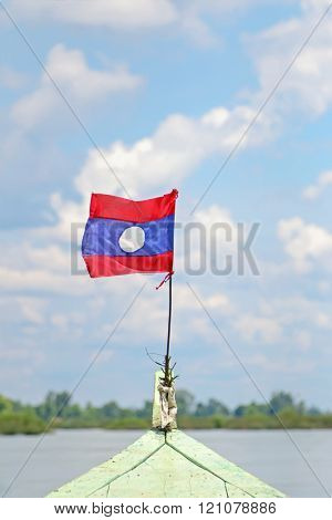 Flag of Laos attached on long tailed boat with blurred background of the Mekong River in Laos