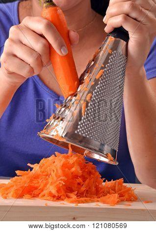 Woman grating carrot.