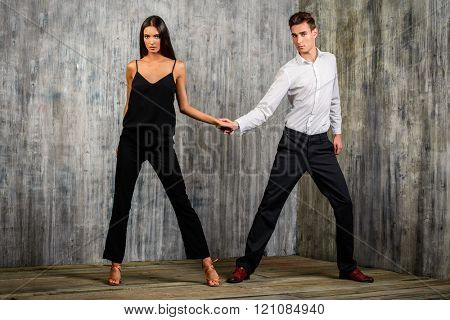 Beautiful young couple in love dancing tango with passion. Professional dancers. Latino dancers.