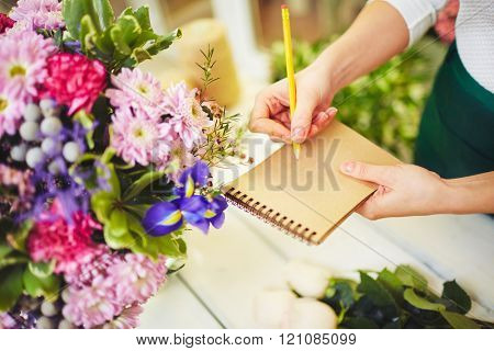 Close-up of florist making notes in notebook
