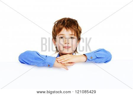 Portrait of a cute 7 year old boy standing with white board. Isolated over white background. Copy space.