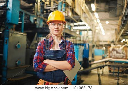 Portrait of young woman in protective glasses in the factory