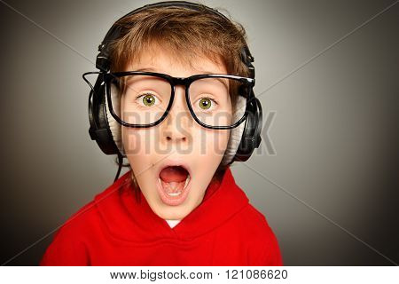 Funny boy gamer in headphones and glasses looking at camera and shouting. Studio shot.