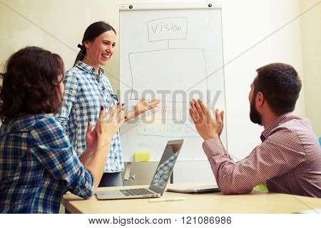 smiley speaker standing near flipchart and pointing at empty copyspace for your text. happy colleagues clapping their hands and looking at speaker