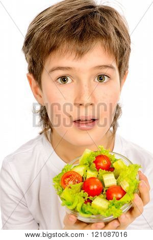 A nine year old boy holding fresh vegetable salad. Healthy eating concept. Isolated over white.