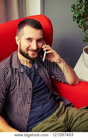 smiley man resting on the chair and talking on the phone