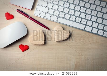 Computer peripherals with hearts, pen and notebook on light wooden table