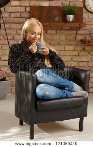 Young casual woman enjoying hot tea at cosy home in armchair. Full size.
