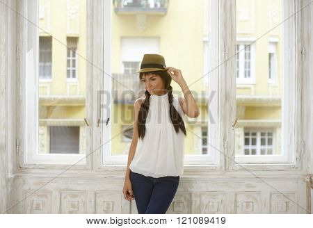 Casual woman in hat with long hair standing at window, looking away, daydreaming.