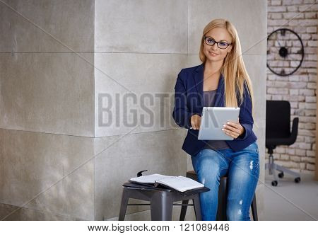 Busy blonde woman working with tablet, using personal organizer.