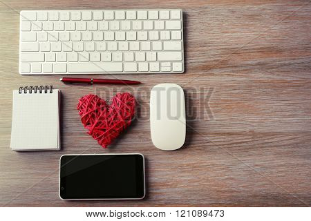 Computer peripherals with red wicker heart, notebook and mobile phone on wooden table