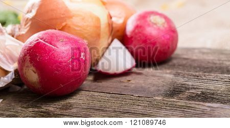 Vegetables - A Garden Radish And Onions - It Is Large Against From Gray Old Boards