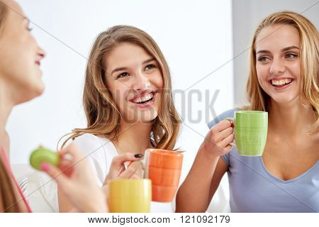friendship, people, pajama party and communication concept - happy friends or teenage girls drinking, chatting tea and eating sweets at home