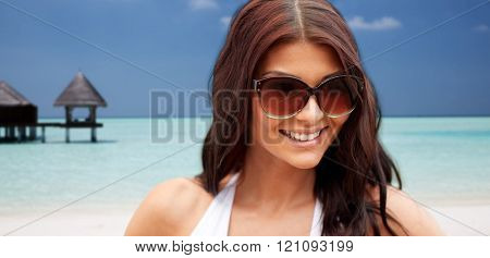summer vacation, tourism, travel, holidays and people concept -face of smiling young woman with sunglasses over bungalow on beach background