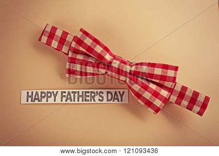 Happy fathers day sticker and bow tie on beige background