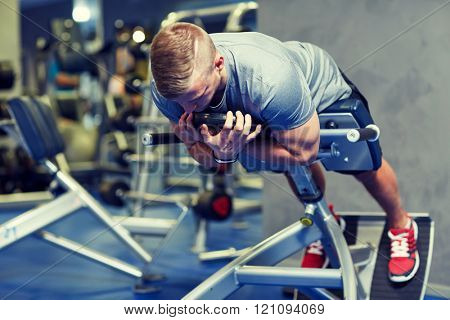 sport, fitness, bodybuilding, lifestyle and people concept - young man flexing back and abdominal muscles on bench in gym
