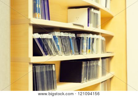 technology, storage and audio media concept - close up of shelving with cd records at recording studio or radio station