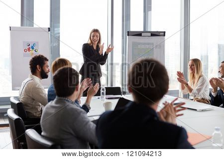 Business people clapping hands during the meeting in modern office.