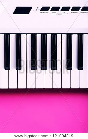 Keyboard of synthesizer on pink background