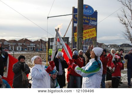 MILTON, CANADA - DECEMBER 19: Passing of the flame between two torch bearers during the Olympic Torch Relay journey in preparation for the 2010 Winter Olympics. Milton, December 19, 2009.