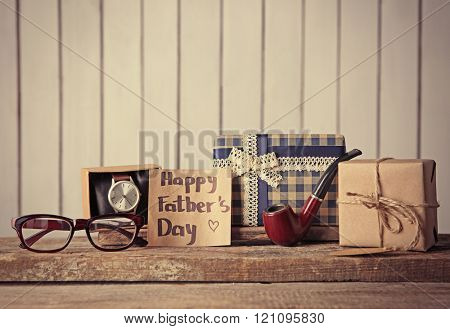 Greeting card for Happy Father's Day with gift boxes, pipe, glasses and watch on wooden table
