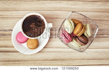 Cup of black coffee with french colorful macarons, view from above