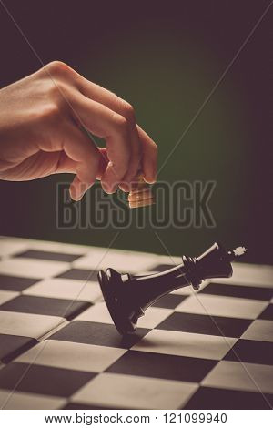 Close-up image of a hand moving a chess piece and defeating the challenger.