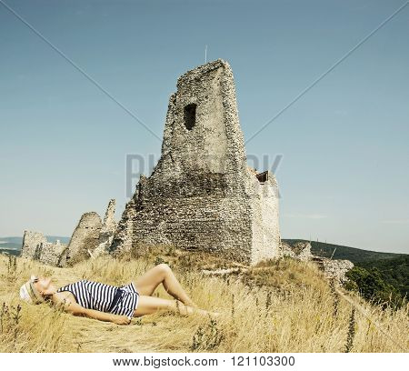 Young caucasian woman in a sailor outfit lying on the dry grass and behind is the castle Cachtice, S
