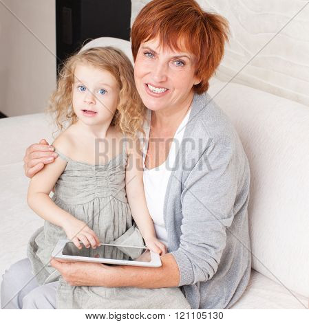 Family wiht tablet computer at sofa. Grandmother and little girl at home on sofa. Generation