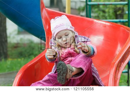 Little girl sitting on red plastic playground slide and tying shoelaces of her kids trainers