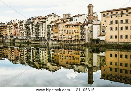 Old buildings with bell tower mirrored in the river Arno, Florence, Italy