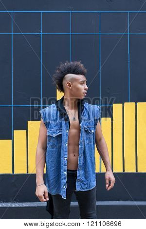 Young african-american man posing against a street wall.