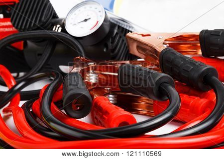 Close up low angle on a coiled set of red and black starter cables or jump leads and a pressure gauge for a car.