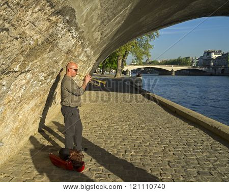 PARIS, FRANCE - APRIL 9 2014: The man playing the trumpet under the bridge on the banks of the River Seine. Sunny evening, close to the Louvre museum.