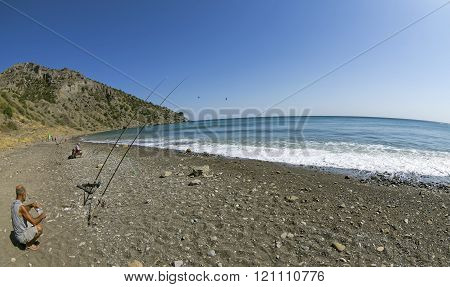 Crimea September 9 2014. Sea fishing near the village of Veseloe. A fisherman with a fishing rod sitting on a deserted beach.