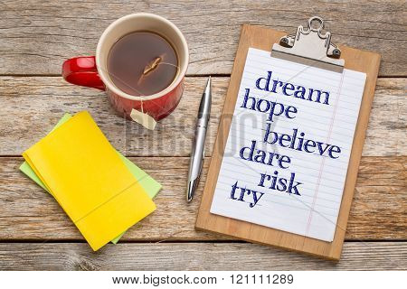 Dream, hope, believe,dare,risk and try - inspirational words on clipboard  with a pen, tea and sticky notes against rust wood table- office concept
