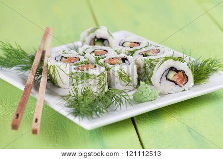 Uramaki sushi with cucumber, raw salmon and dill