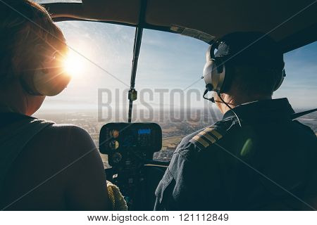 Two pilots in a helicopter while flying on a sunny day