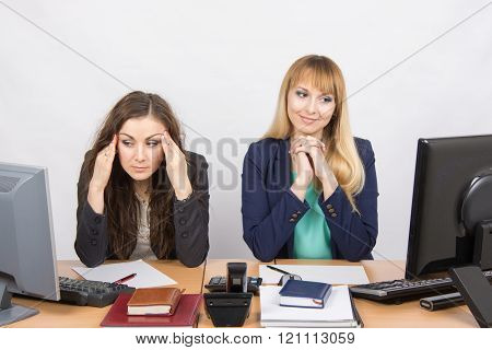The Situation In The Office - Girl Happily Looking At A Computer Screen, The Other A Girl With A Hea