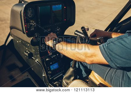 Pilot's Hand On An Helicopter Instrument Panel.