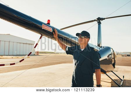 Pilot Standing At The Tail Of A Helicopter