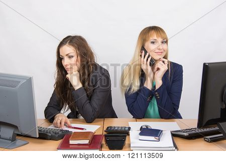 The Situation In The Office - Happy Employee Talking On Phone, Colleague Looking Wearily At The Comp